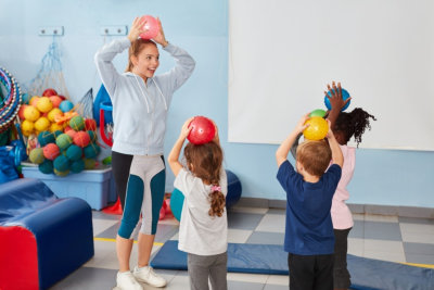 children play with balls in the gym together with kindergarten teacher