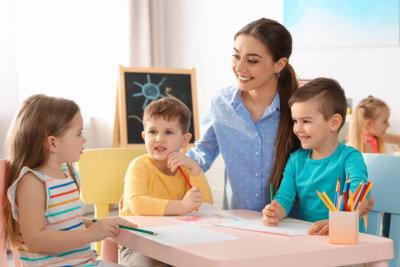 Little children with kindergarten teacher drawing at table indoors