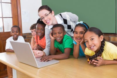 teacher and pupils working at laptop