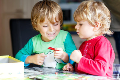 Two little blond kid boys playing together