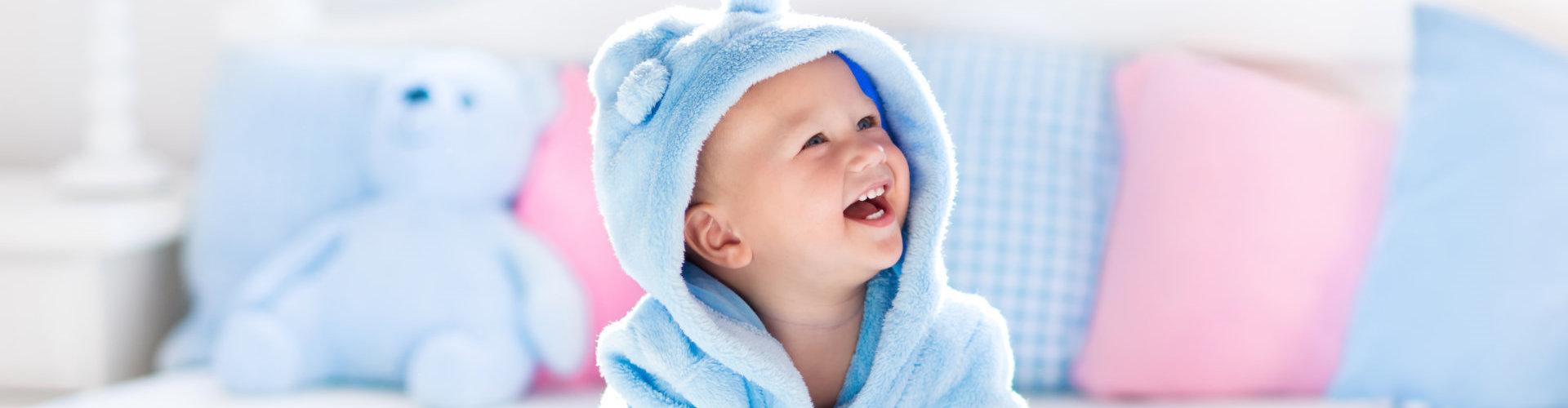 Cute happy laughing baby boy in soft bathrobe after bath playing